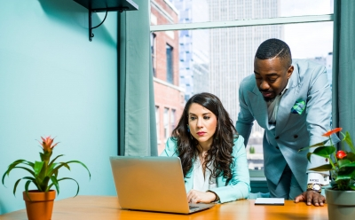 man and woman working at a desk on a computer